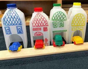 4 empty Procal milk bottles that have been crafted into four makeshift houses with carports.