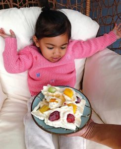 Little girl sitting on the couch with a plate of Frozen Yoghurt bark on a plate on her lap with her arms up in excitement